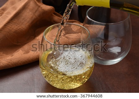 Pouring white wine into a glass, high speed photography, focus on pour - stock photo