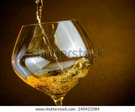 pouring white wine into a glass on golden background with space for text, warm atmosphere
