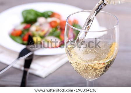 Pouring white wine into glass and food background - stock photo
