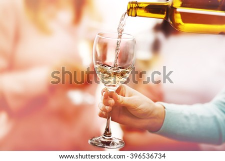 Pouring white wine into glass at hen-party, close up - stock photo