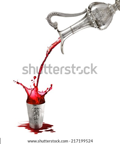 pouring wine from silver pitcher into silver cup - stock photo