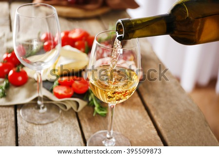 Pouring wine into glass and food on wooden table closeup