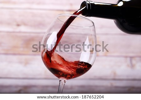Pouring wine into glass and wooden background