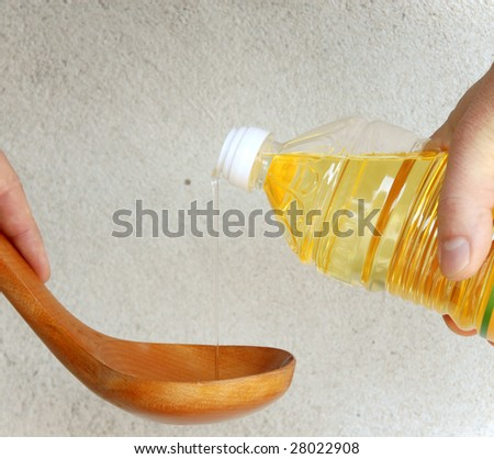 pouring yellow vegetable oil into wooden spoon over gray background