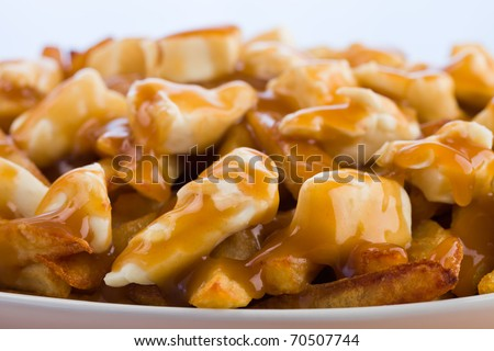 Poutine meal made with french fries, cheese curds and gravy. Macro photography with shallow depth of field. - stock photo