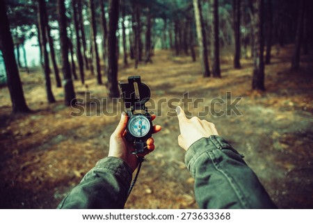 POV image of traveler woman holding a compass and pointing direction in the forest. Image with instagram color effect - stock photo