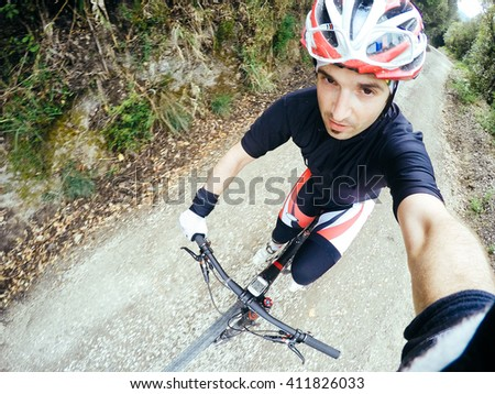 POV, Original point of view. Young man on bicycle take a selfie. Training on mountain bike on a mountainous road.