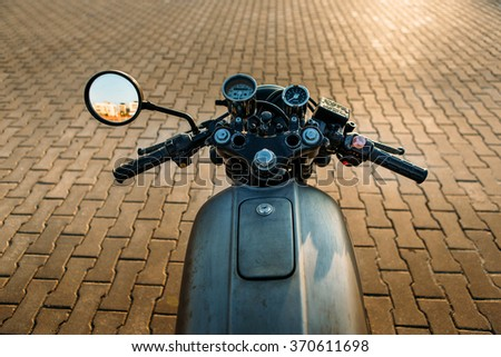 POV silver vintage custom motorcycle motorbike caferacer on empty rooftop parking lot with city center with urban environments midtown buildings in side mirror. Hipster lifestyle. - stock photo
