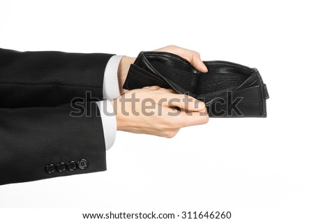 Poverty and money theme: a man in a black suit holding a empty purse isolated on white background in studio - stock photo