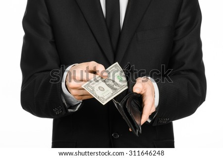 Poverty and money theme: a man in a black suit holding a empty wallet and banknote 1 dollar on white isolated background in studio