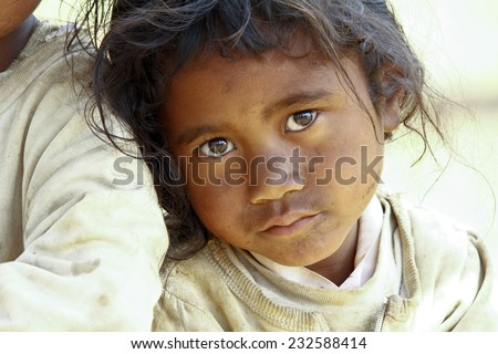 Poverty, portrait of a poor little African girl lost in deep thoughts - stock photo