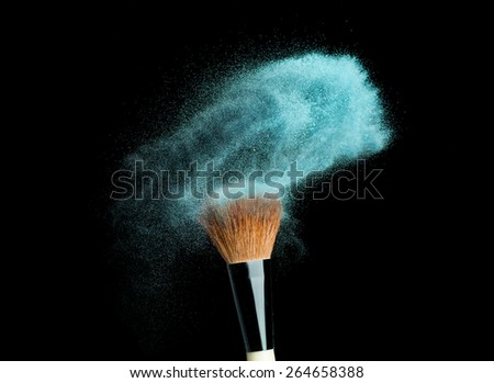 powder brush on black background with blue powder splash  close up - stock photo