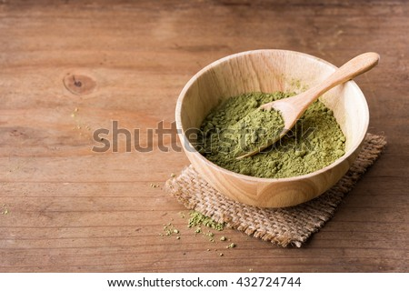 powder green tea in wooden bowl on wooden background,close up green tea powder on wooden table