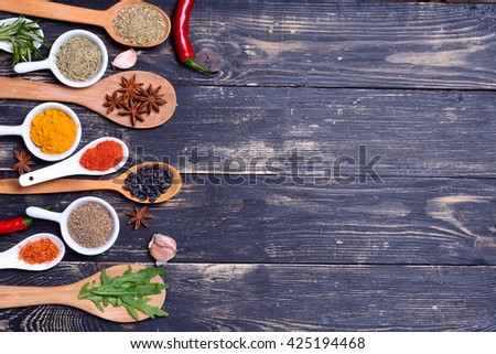 Powder spices & herbs on spoons in black wooden table background - stock photo