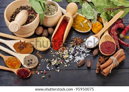 Powder spices in different spoons on black wooden rustic surface - stock photo