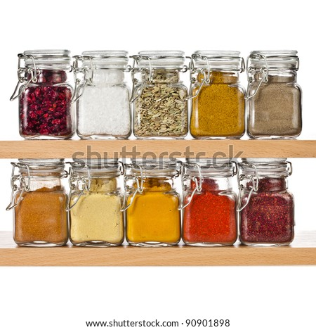 powder spices in glass bottle jar on a wooden shelf ,  isolated on white background - stock photo