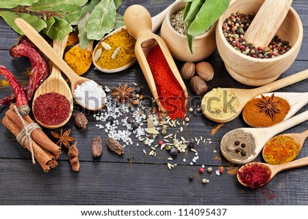 Powder spices on spoons in black wooden table background