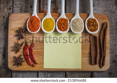 Powder spices on spoons in vintage wooden table background - stock photo
