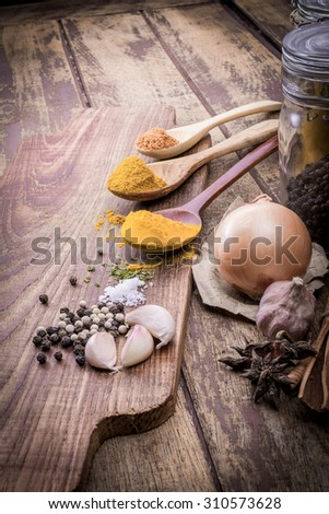 Powder spices on spoons in wooden table background