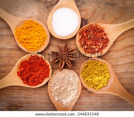 powder spices on spoons on wooden background  - stock photo