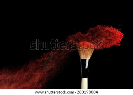 powderbrush on black background with red powder splash close up - stock photo