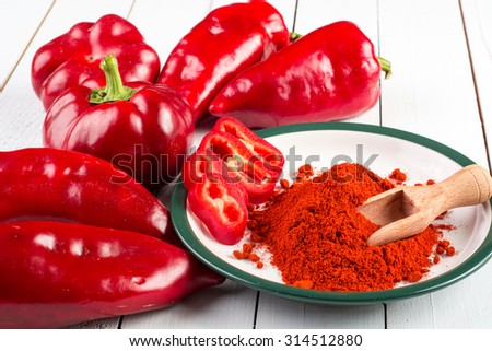 Powdered and fresh red paprika on wooden table - stock photo