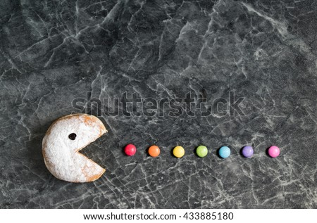 Powdered donut eating colored smarties, candy drops - stock photo