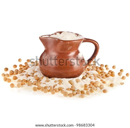 powdered milk drink in a clay jug  with soy beans on white background - stock photo
