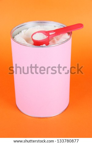 Powdered milk for baby on orange background