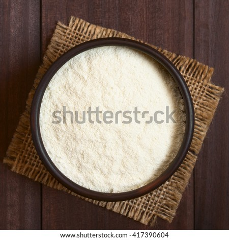 Powdered or dried milk in bowl, photographed overhead on dark wood with natural light (Selective Focus, Focus on the top of the milk powder) - stock photo