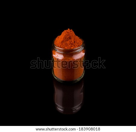 Powdered red chili spices over black background - stock photo