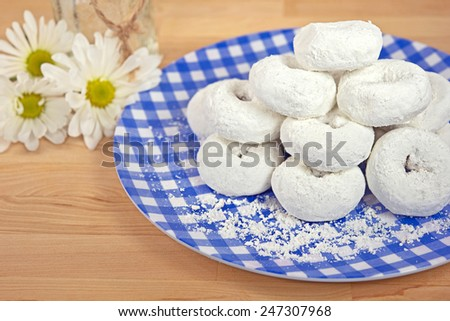 powdered sugar donuts on blue and white gingham plate with daisies - stock photo