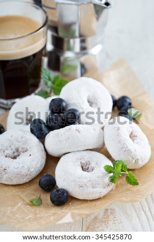 Powdered sugar donuts on parchment with blueberries and mint