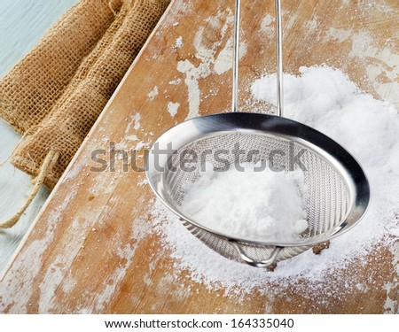 Powdered sugar in a metal sieve on wooden table. Selective focus
