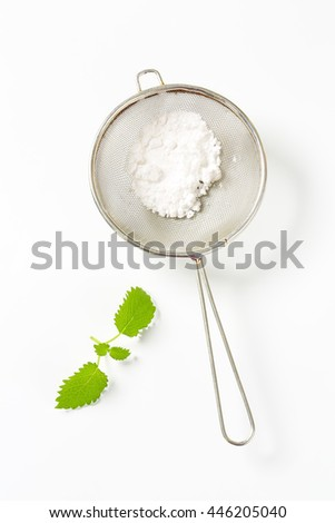 powdered sugar in a sieve - stock photo