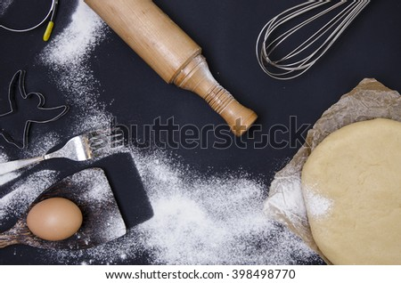 Powdering by flour rolled out dough for bakary stics  with wooden rolling pin over black basground.