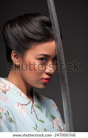 Power and concentration. Side view portrait of young beautiful Japanese woman in kimono holding katana sword by her head and looking at camera while standing against grey background - stock photo