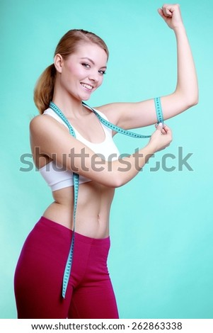 Power and energy. Health care and healthy active lifestyle. Young fitness woman fit girl with measure tape measuring her biceps on blue green - stock photo