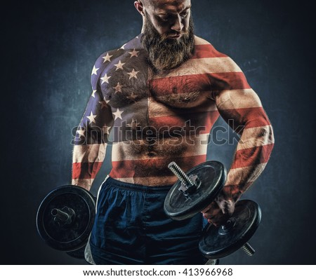 Power athletic bearded man in training pumping up muscles with dumbbell. The body is depicted an American flag. Concept: Captain America.