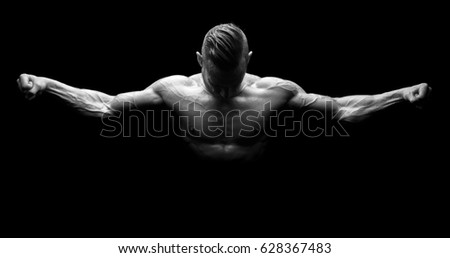 Power athletic man with open arms. Strong bodybuilder with six pack, perfect abs, shoulders, biceps, triceps and chest isolated in a black background