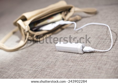 Power-bank in the woman`s bag. - stock photo