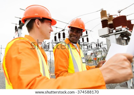 power company electricians discussing blueprint at electrical substation - stock photo