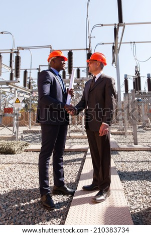 power company managers handshaking in electrical substation - stock photo