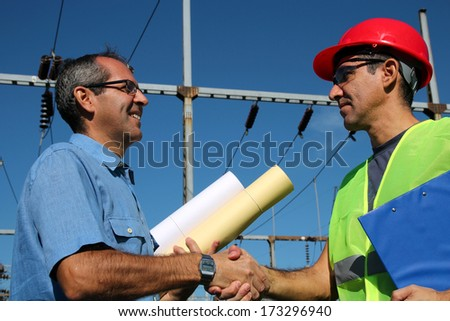 Power Company Workers. Two man handshake. Smiling workers with blueprints and clipboard in meeting at electrical substation.  - stock photo