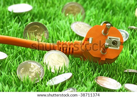 Power connector with euro coins on a grass meadow as background - stock photo
