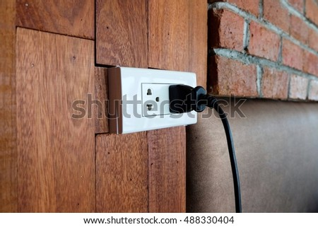 Power electric plug on the wooden wall