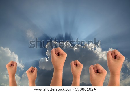 Power fist on sun beam and sky-clouds background.