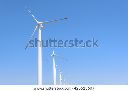 Power generation wind turbines against the blue sky with clouds.