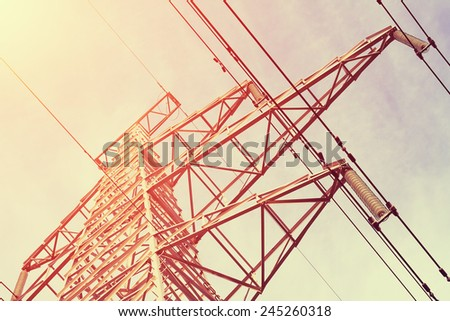 Power Line against sky background at sunrise, cross-processing effect - stock photo
