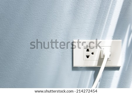 Power line and plug on the wall. - stock photo